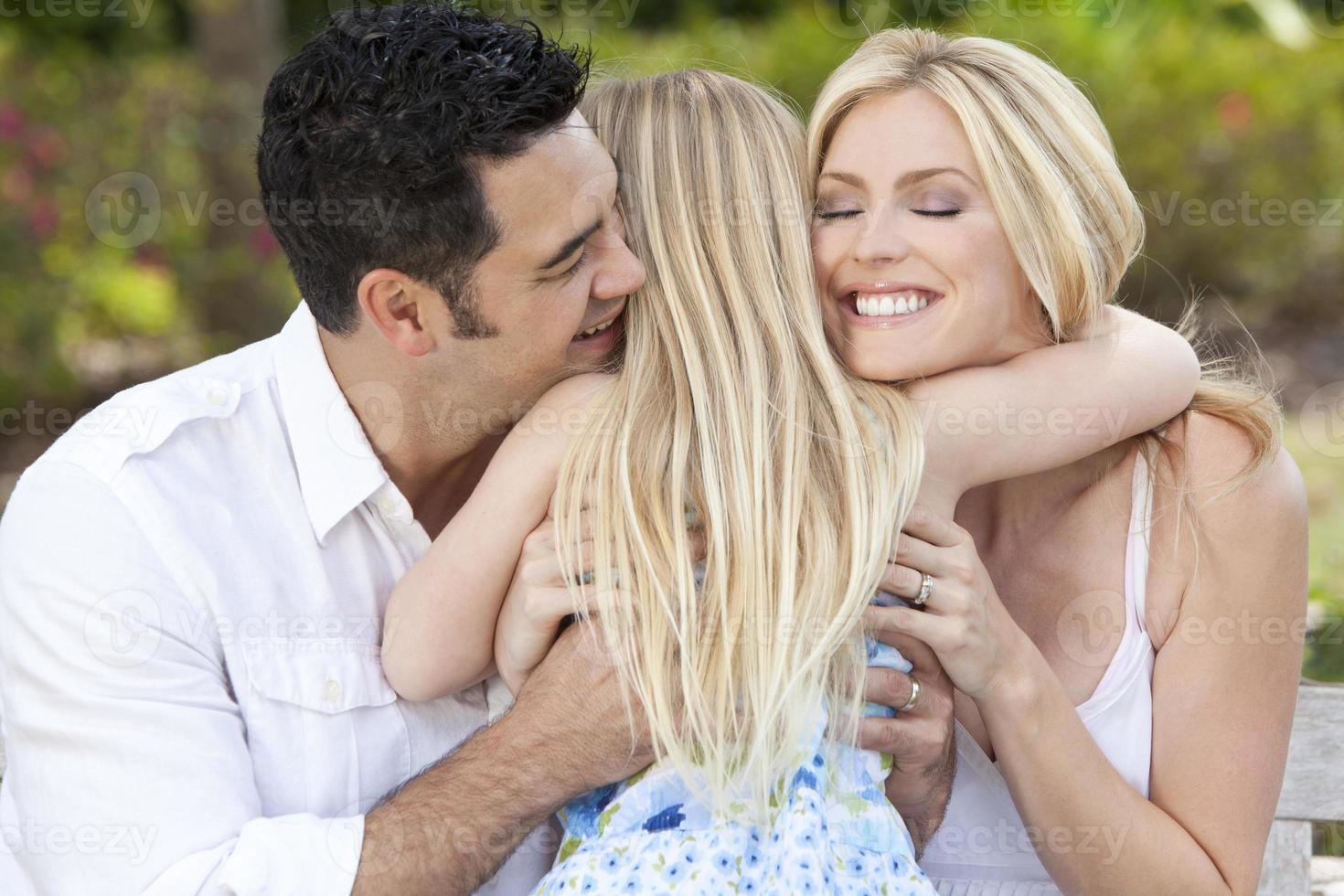 Mädchen, das glückliche Eltern im Park oder im Garten umarmt foto