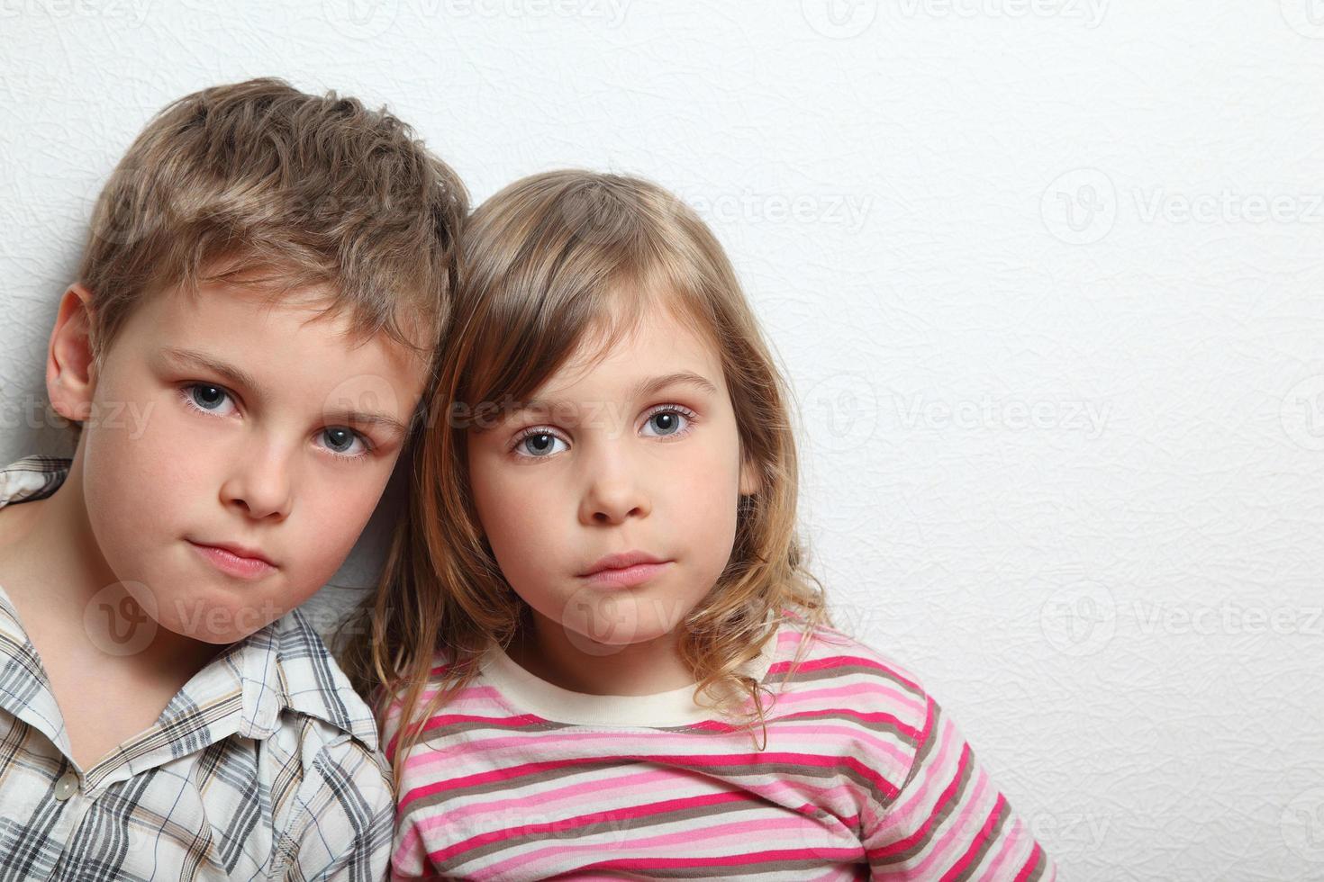 Porträt des nachdenklichen kleinen Mädchens und des Jungen foto