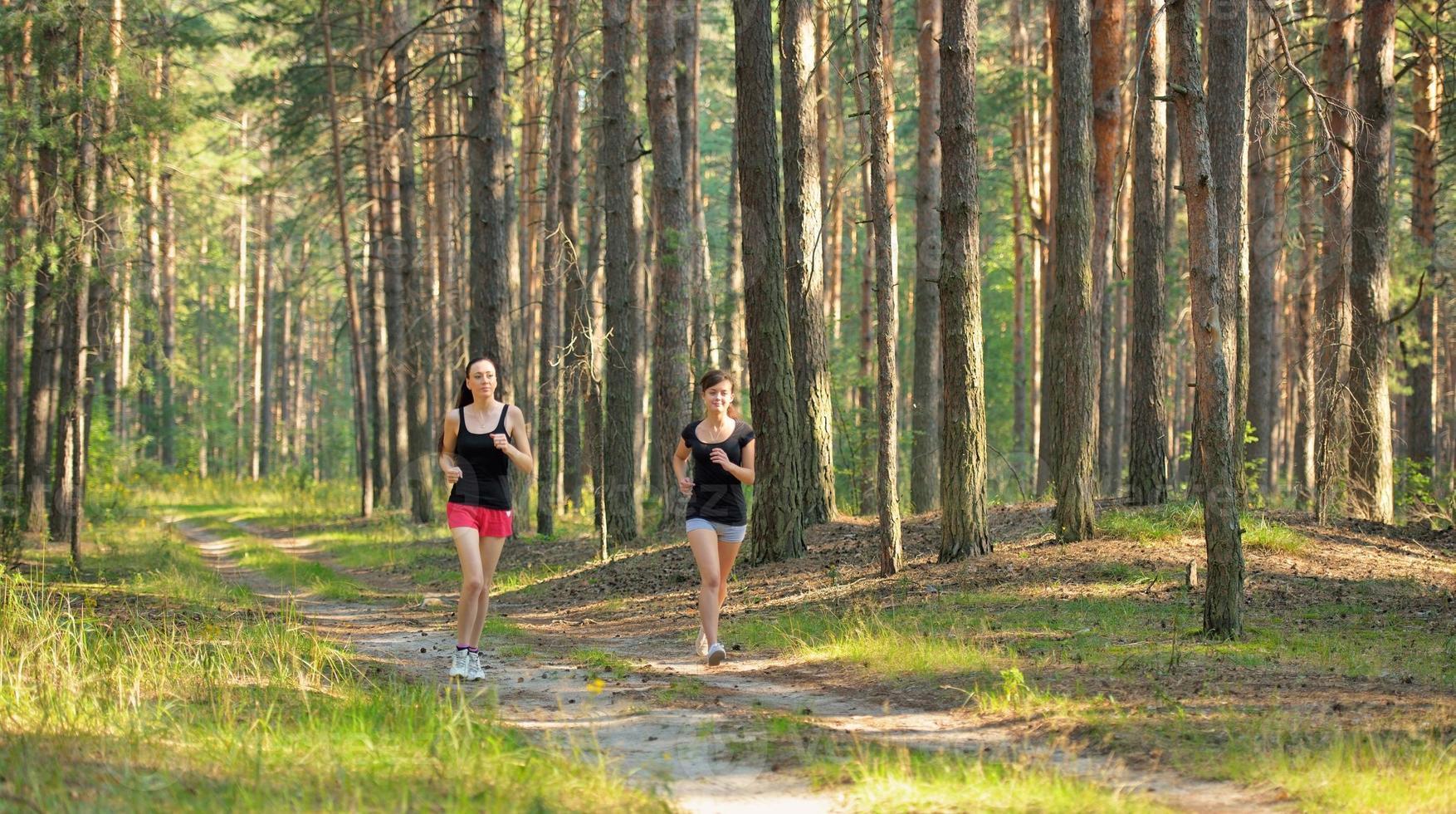 zwei Frau, die im Wald joggt foto