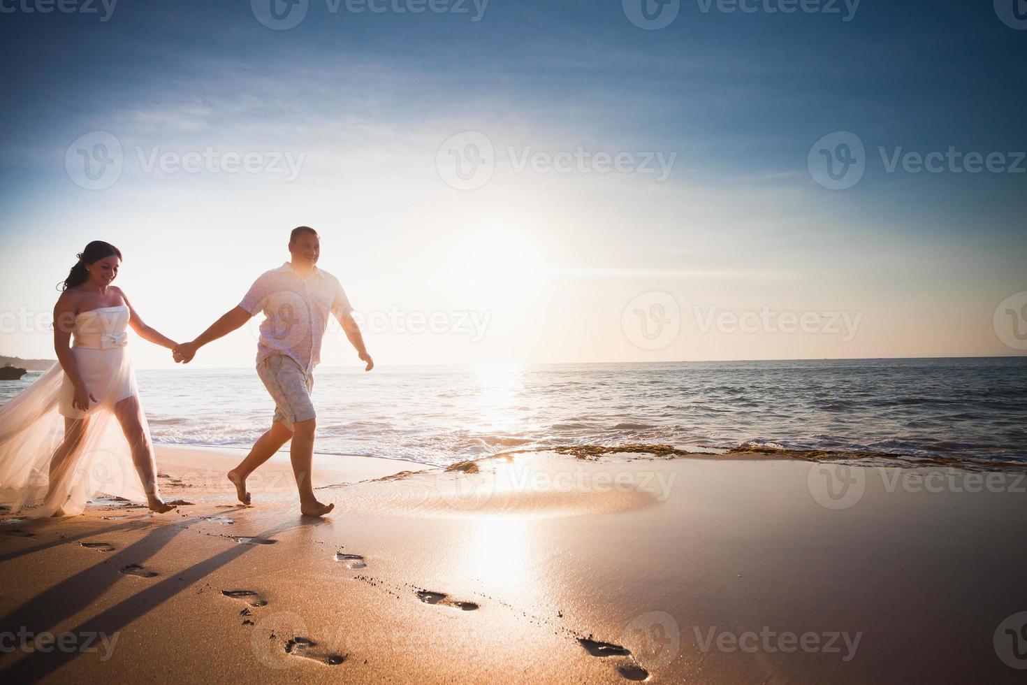 Hochzeitsreisende Ehepaar gerade geheiratet am Strand laufen foto