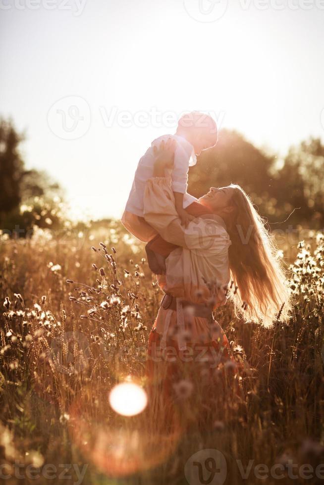 glückliche Mutterkommunikation mit Sohn in einem Weizenfeld foto