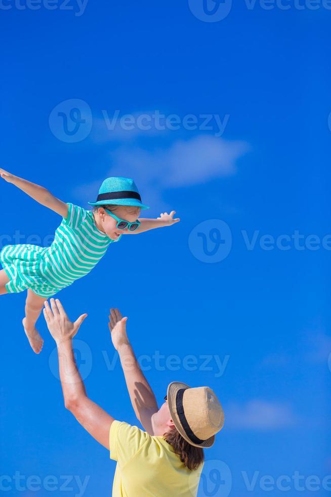 glücklicher Vater, der Spaß mit kleinem Kind während des Strandurlaubs hat foto