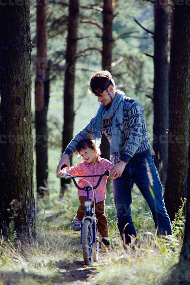 Vater lernt seinen Sohn, draußen in draußen Fahrrad zu fahren foto