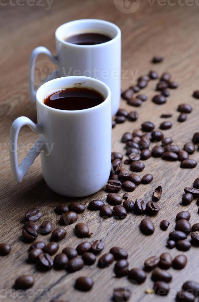 zwei Tassen Expresso, umgeben von Kaffeebohnen foto