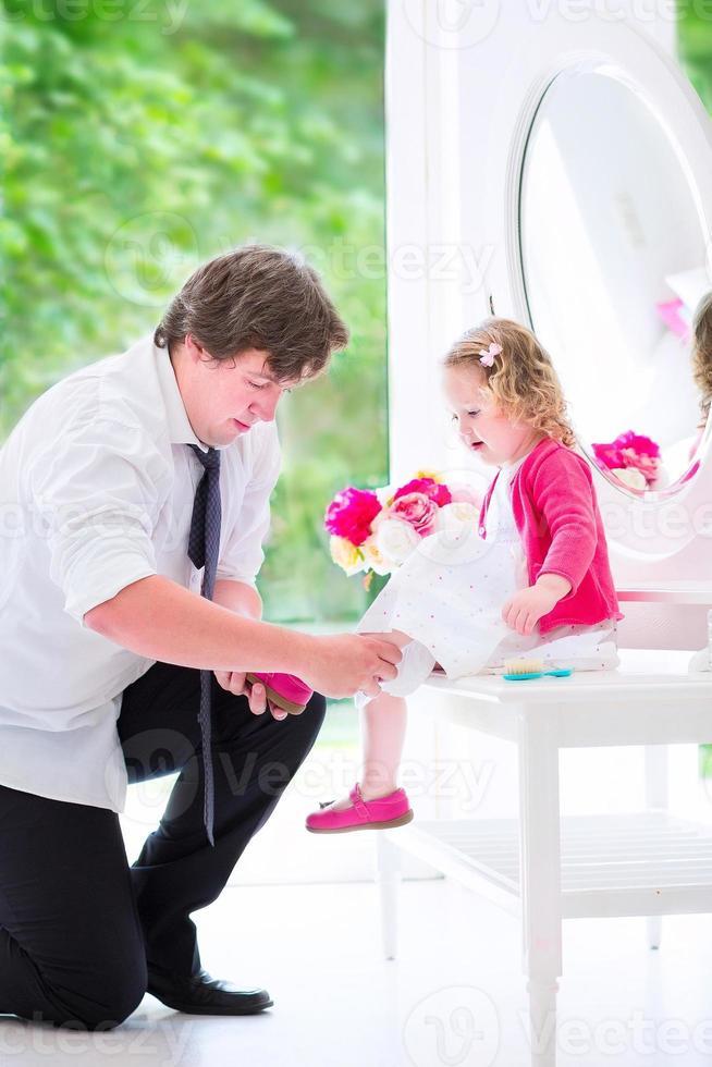 Vater zog einen Schuh seiner entzückenden Tochter an foto