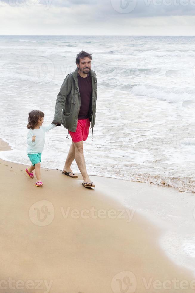 authentisches Foto über Vater und Tochter am Strand spazieren