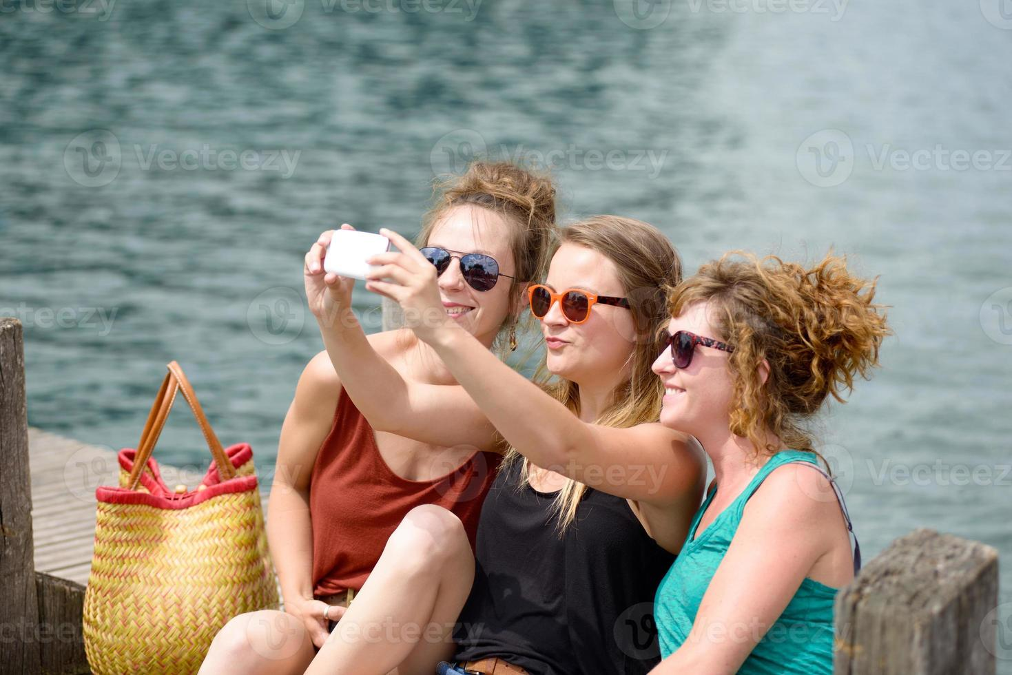 drei junge Frau am Strand mit ihrem Telefon foto
