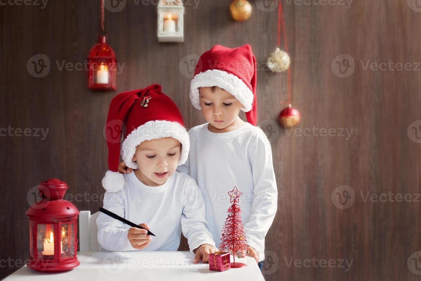 zwei entzückende Jungen, die einen Brief an den Weihnachtsmann schreiben foto