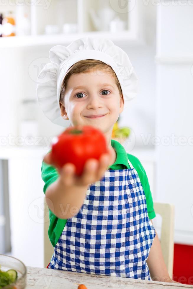 kleiner niedlicher Kinderjunge mit Kochhut, der Tomate hält foto