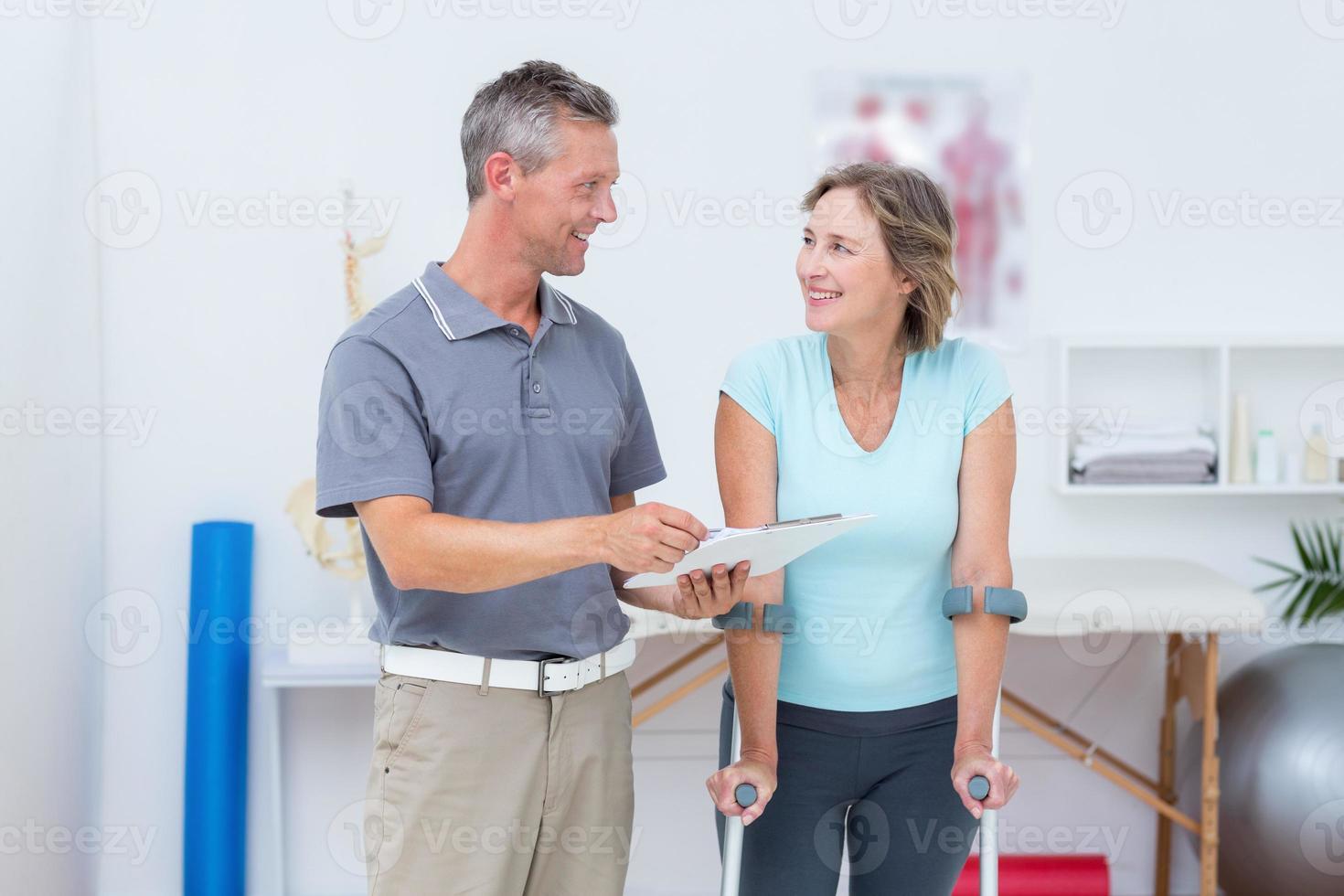 Frau mit Krücke und im Gespräch mit ihrem Arzt foto