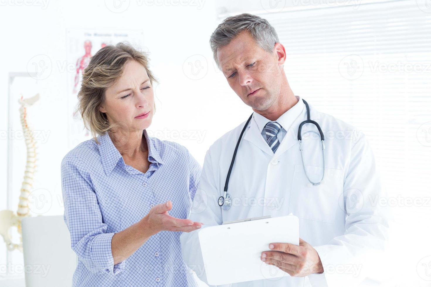 Arzt zeigt dem Patienten seine Notizen foto