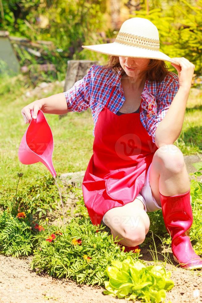 Frau, die Pflanzen im Garten gießt foto