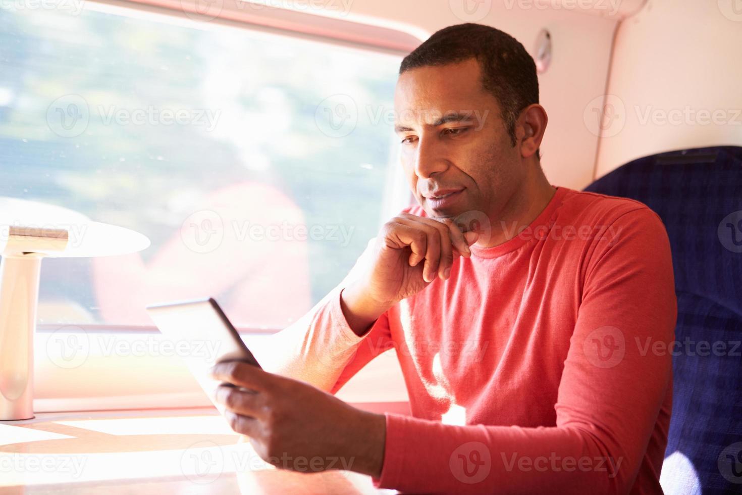 Mann, der ein elektronisches Buch in einem Zug liest foto