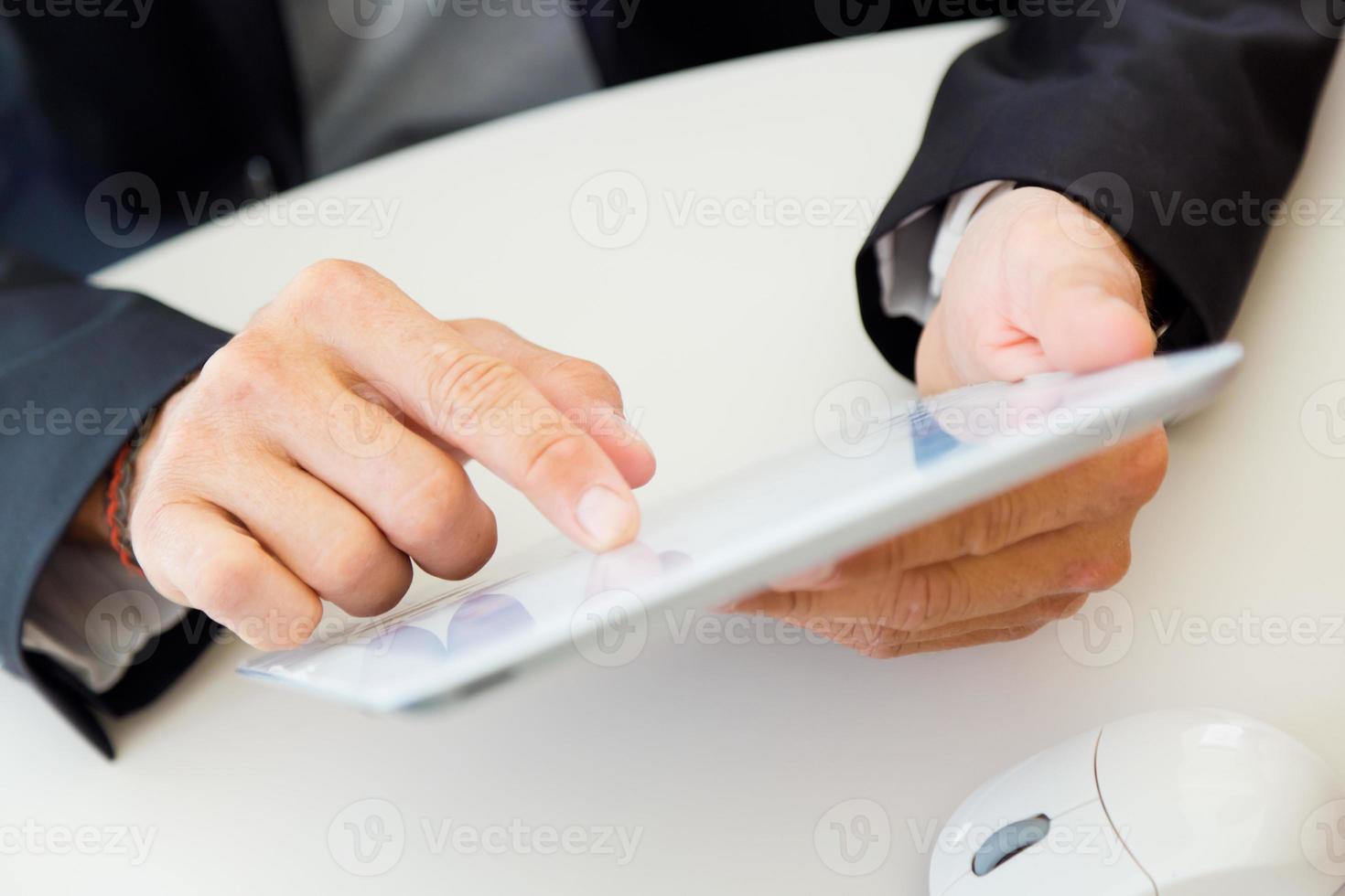 Geschäftsmannfinger, der auf den Bildschirm eines digitalen Tablets zeigt. foto