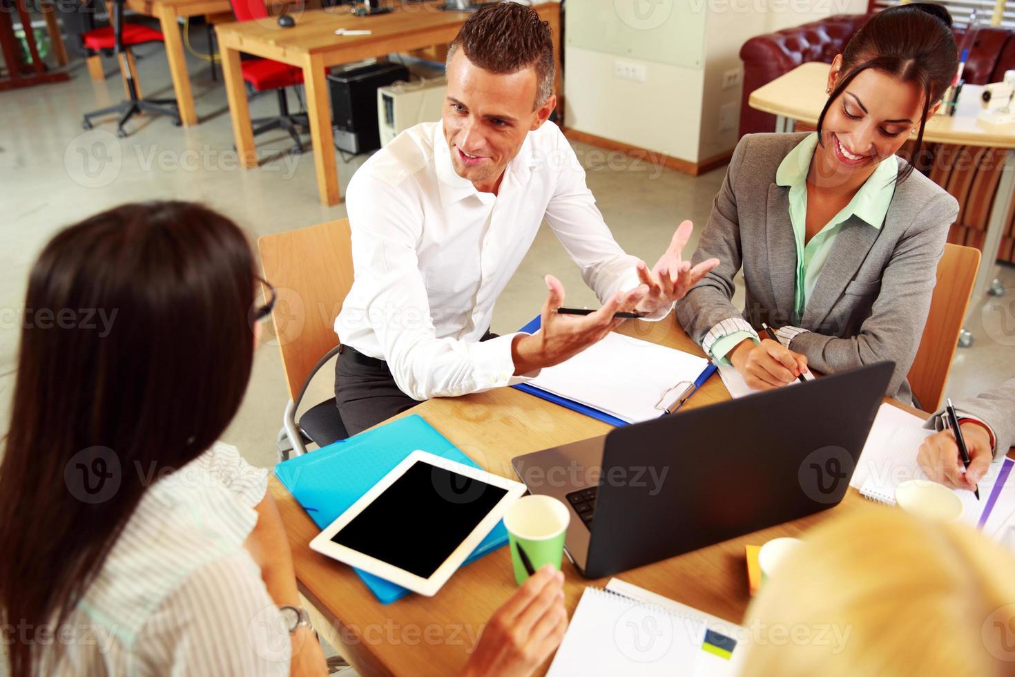 Geschäftsleute, die sich um den Tisch treffen foto