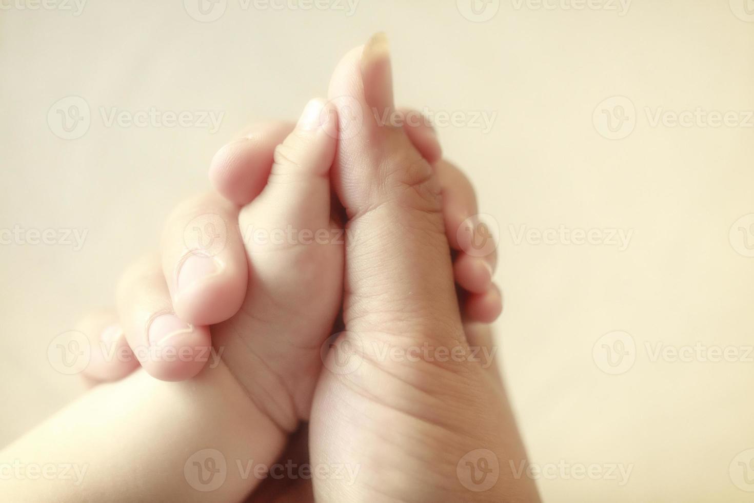 Baby hält den Finger seiner Mutter, selektiver Fokus foto