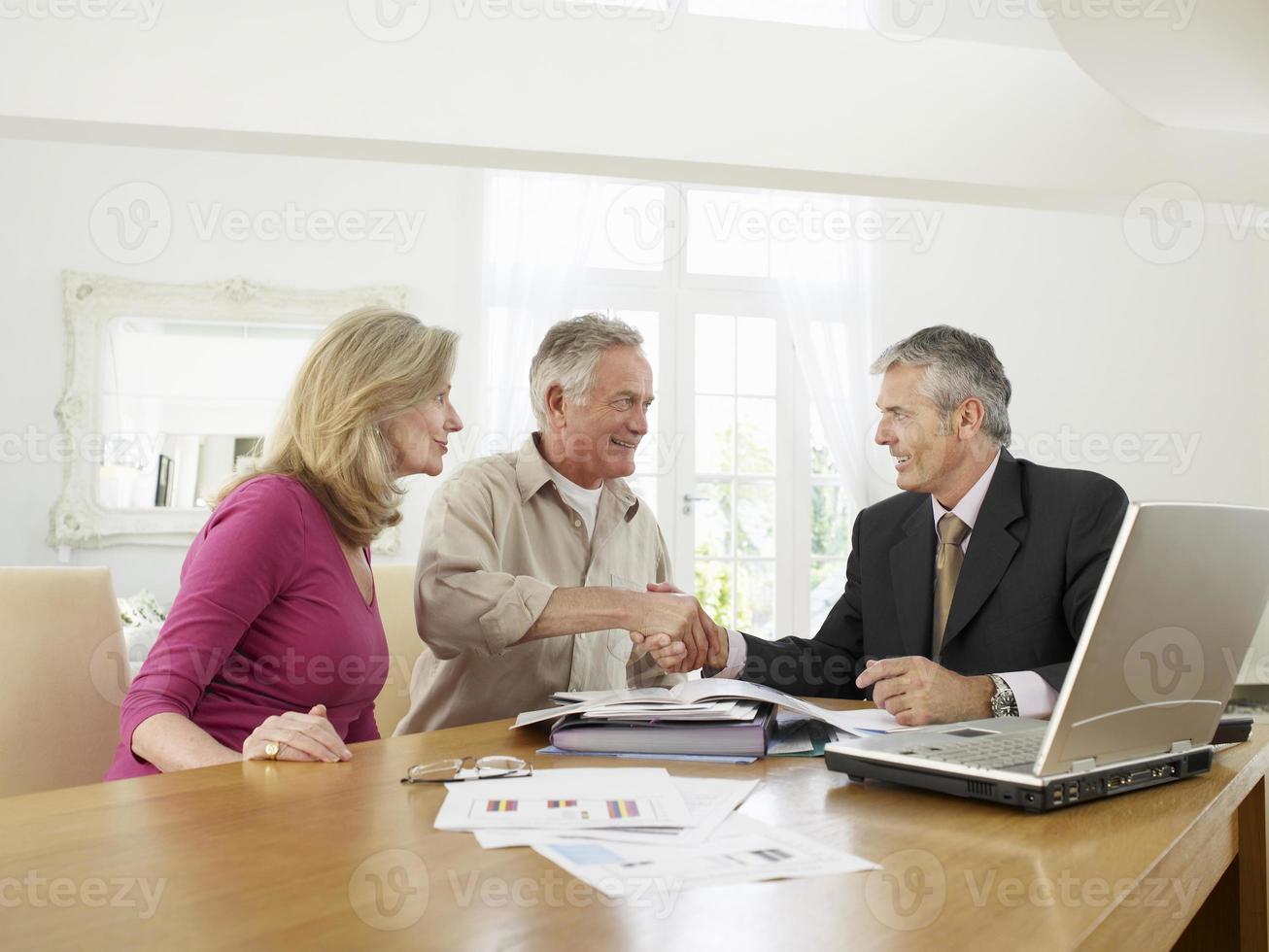 Paar mit Finanzberater am Tisch foto