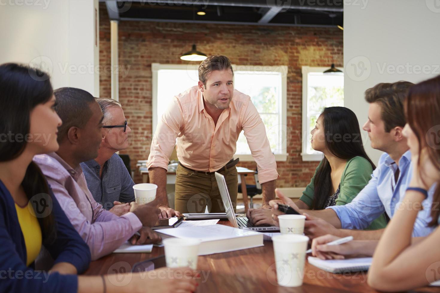 männlicher Chef, der Büroangestellte beim Treffen anspricht foto