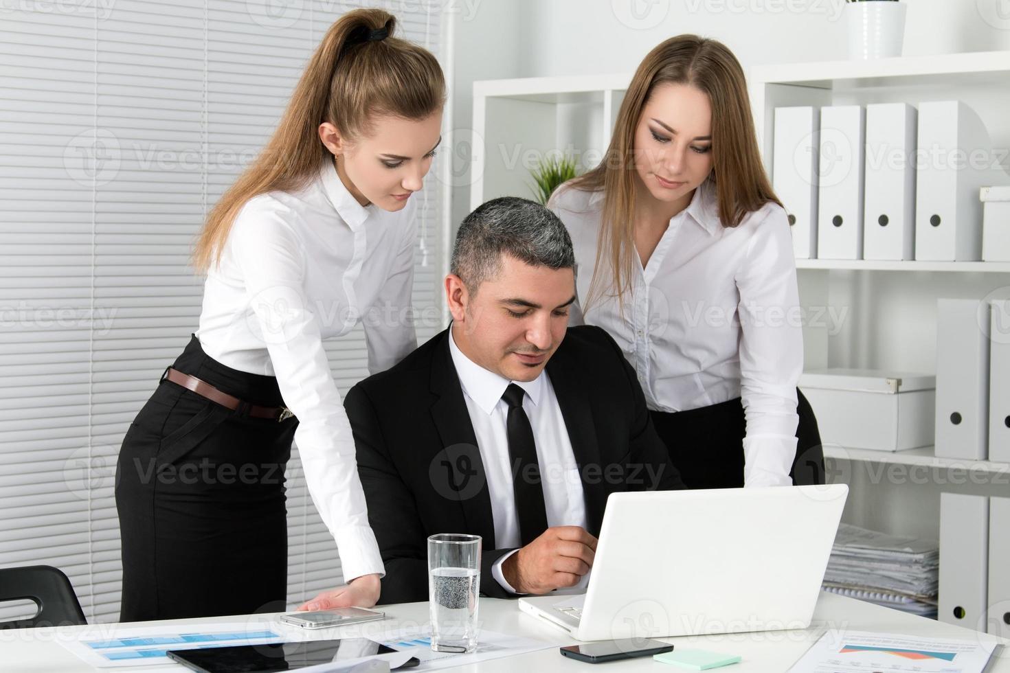 zwei junge schöne Geschäftsfrauen, die mit ihrer Kollegin beraten foto