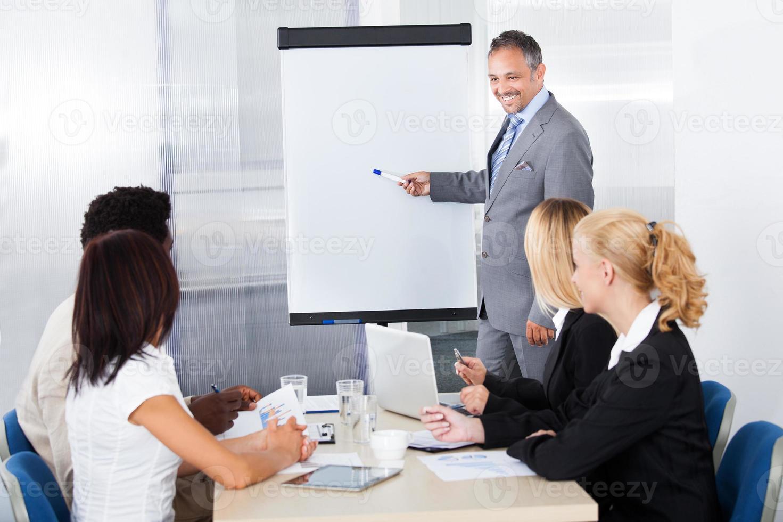 Geschäftsleute, die den Mann betrachten, der erklärt foto