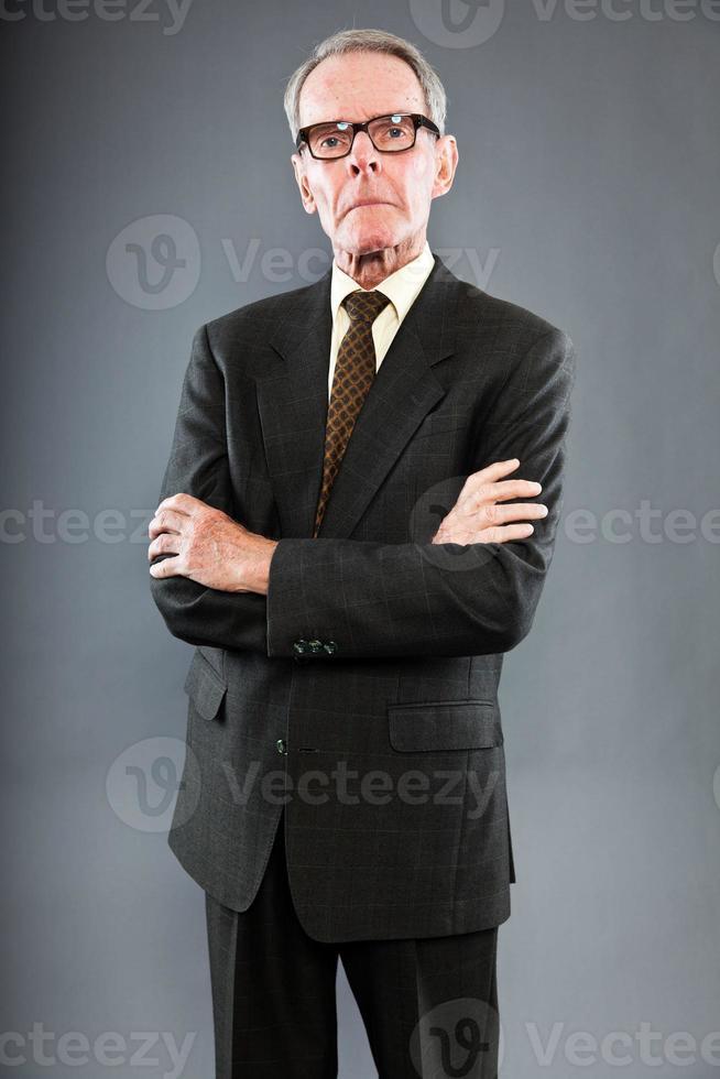 ausdrucksstarker gut aussehender älterer Mann, der dunklen Anzug und Brille trägt. foto