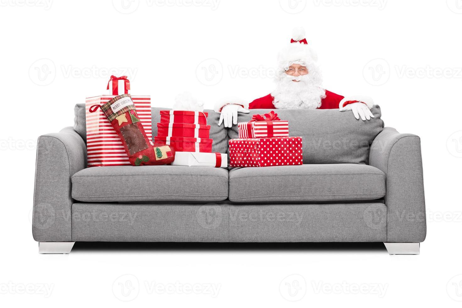 Weihnachtsmann versteckt sich hinter einem Sofa voller Geschenke foto