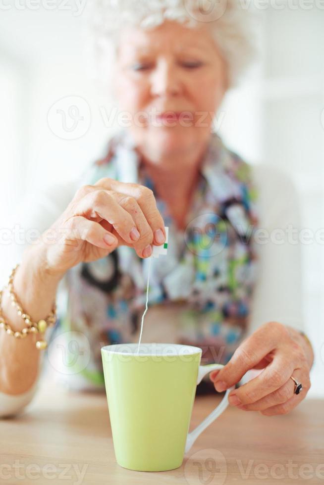 alte Dame hält einen Teebeutel foto