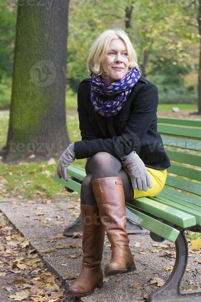 Frau sitzt auf einer Bank foto
