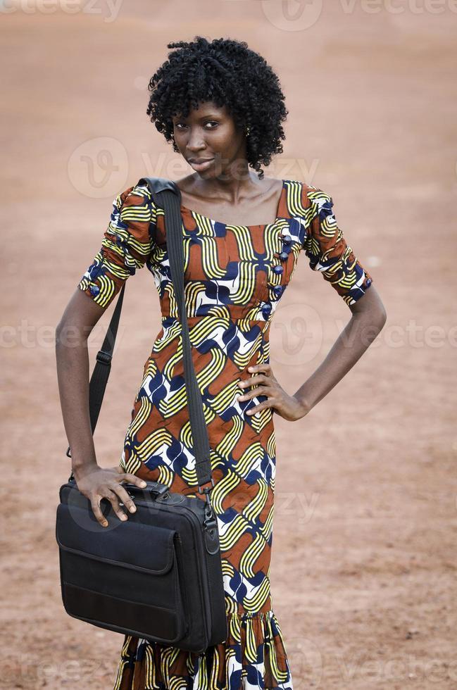 Universitätssymbol: afrikanisches schwarzes Mädchen, das Computertasche hält foto