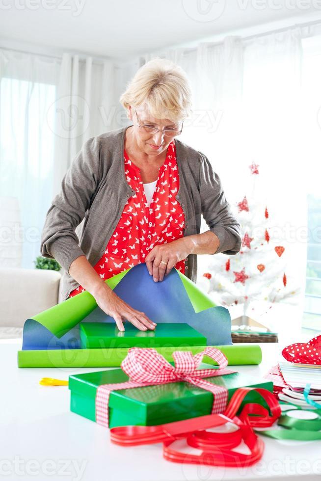 Frau, die Weihnachtsgeschenke einwickelt foto