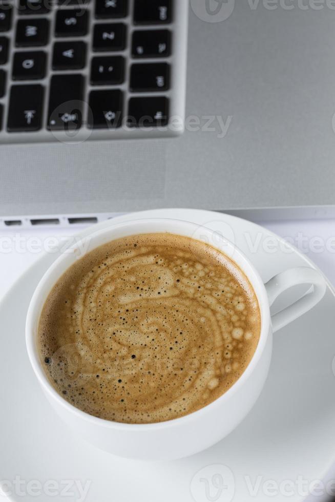 Tasse Kaffee in einer weißen Tasse auf einem weißen Teller foto