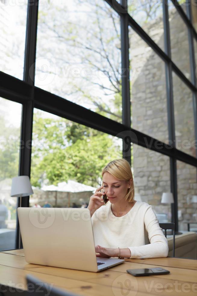 Geschäftsfrau sprechen auf dem Smartphone und schauen auf den Netbook-Bildschirm foto