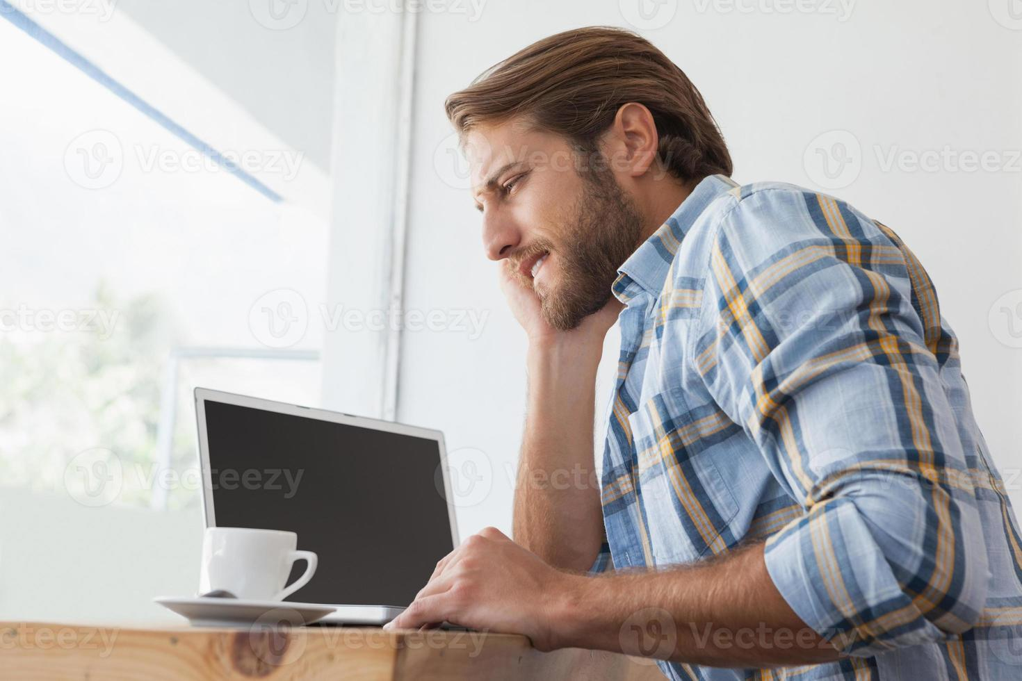Gelegenheitsmann mit Laptop beim Kaffee foto