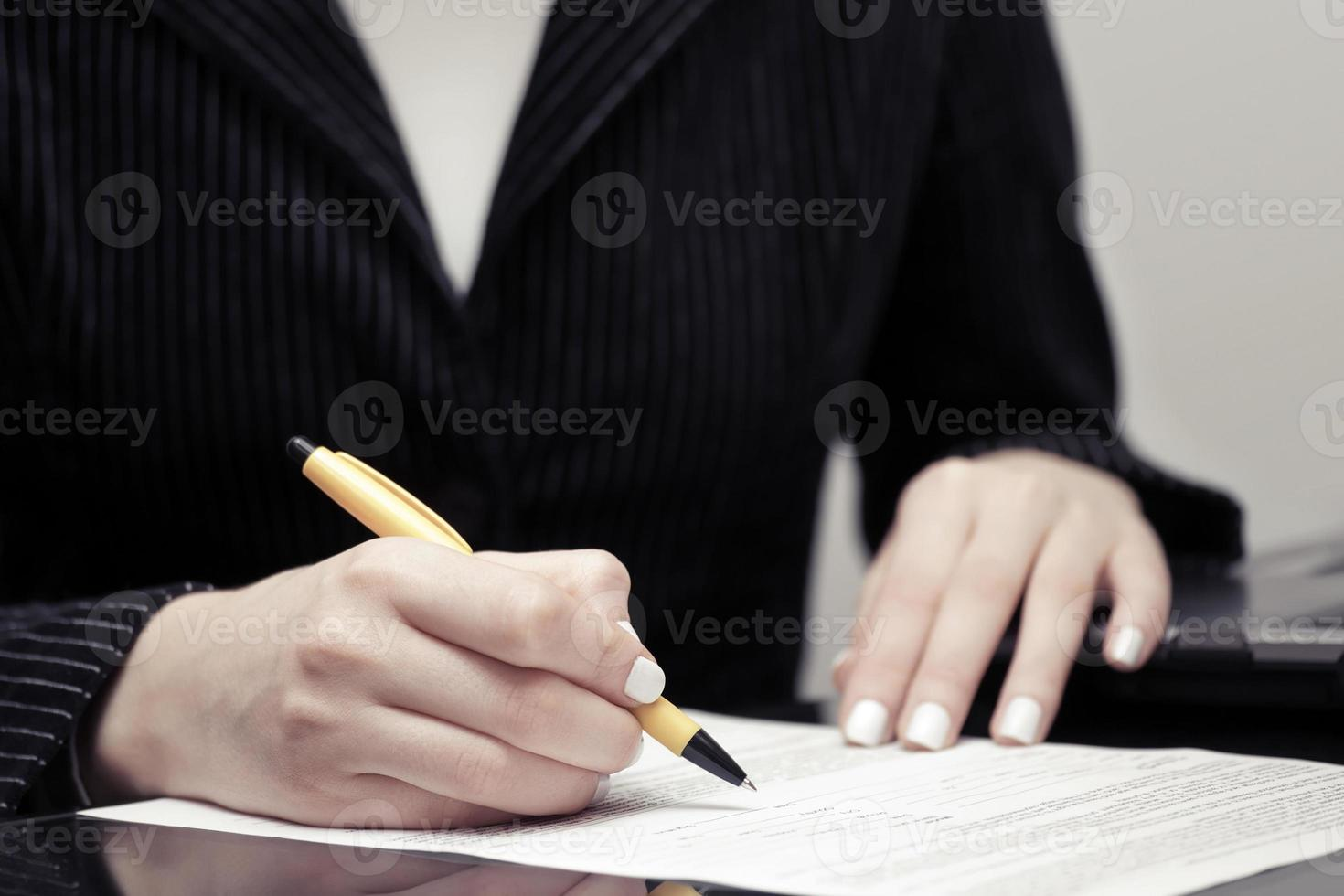 Geschäftsfrau unterschreibt Vertrag foto