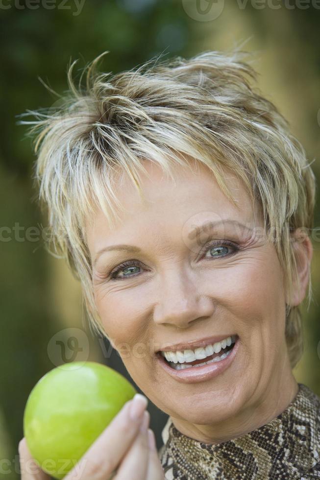 Frau, die Apfel draußen hält, Porträt foto
