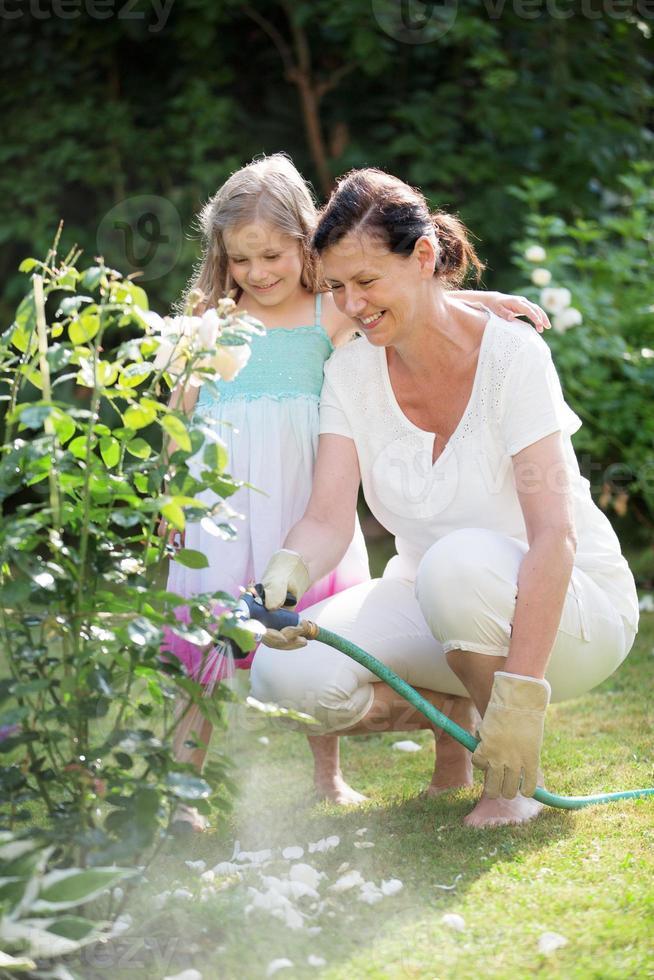 Mädchen und Oma gießen Blumen im Garten foto