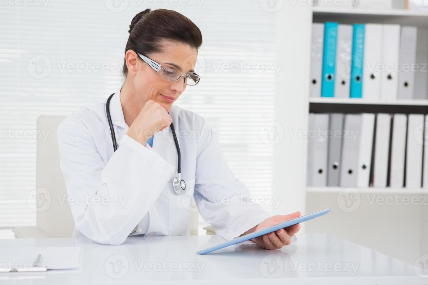 Tierarzt sitzen und Tablette halten foto
