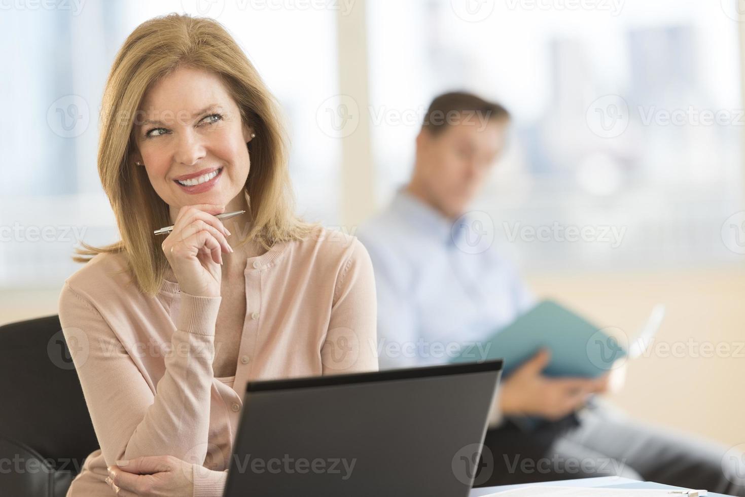 nachdenkliche Geschäftsfrau, die im Büro lächelt foto