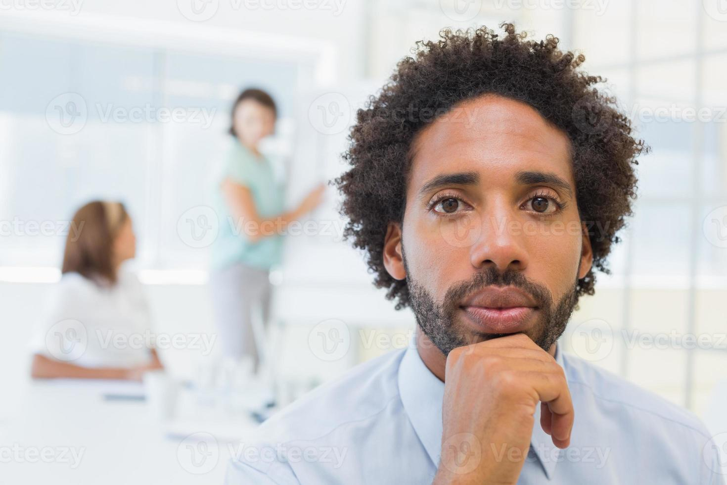 ernsthafter Geschäftsmann mit Kollegen im Treffen im Büro foto