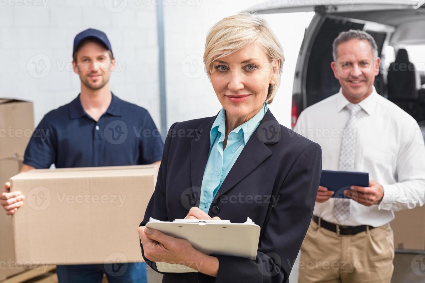lächelnder Manager hält Zwischenablage vor seinen Kollegen foto
