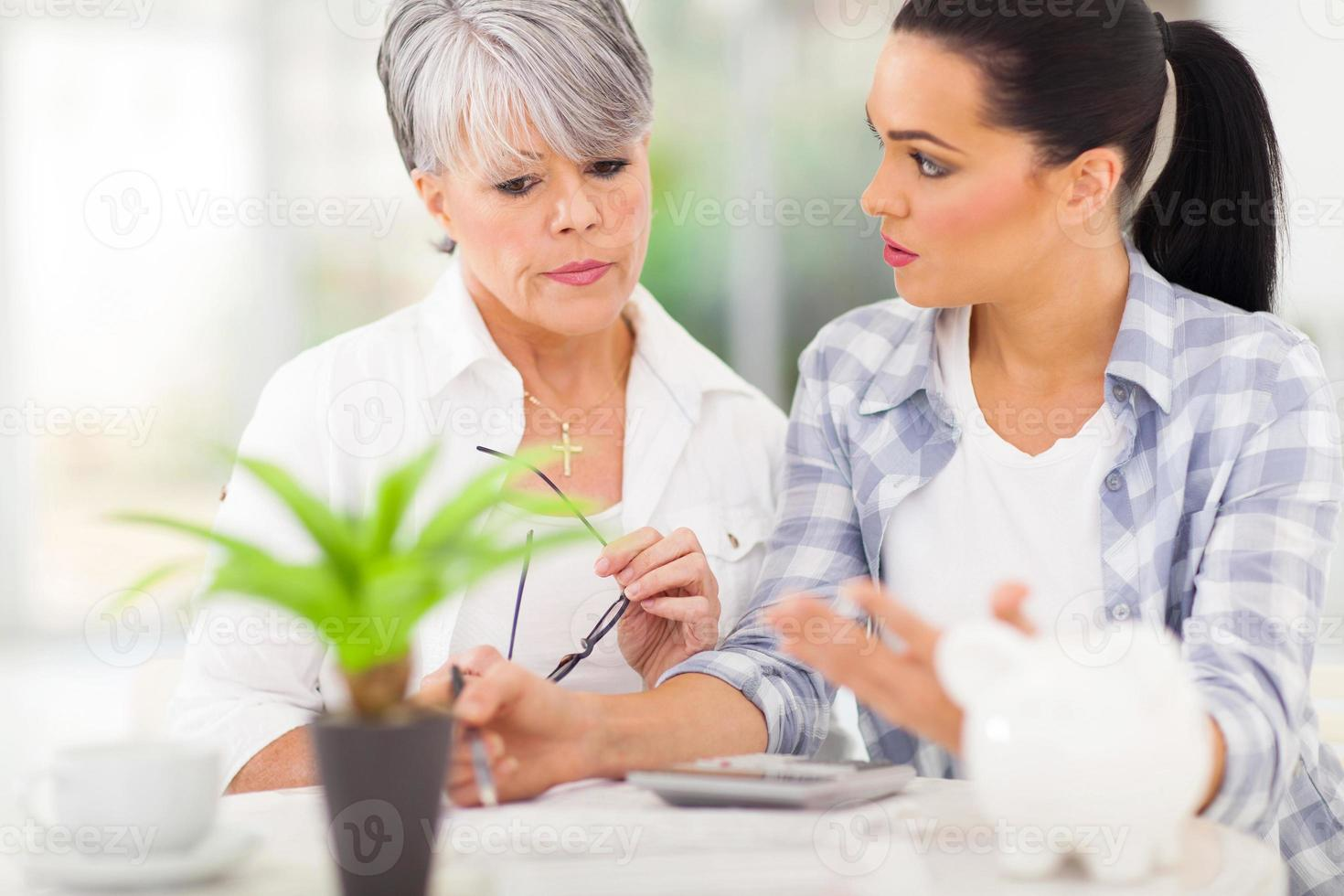 erwachsene Tochter hilft älterer Mutter bei ihren Finanzen foto
