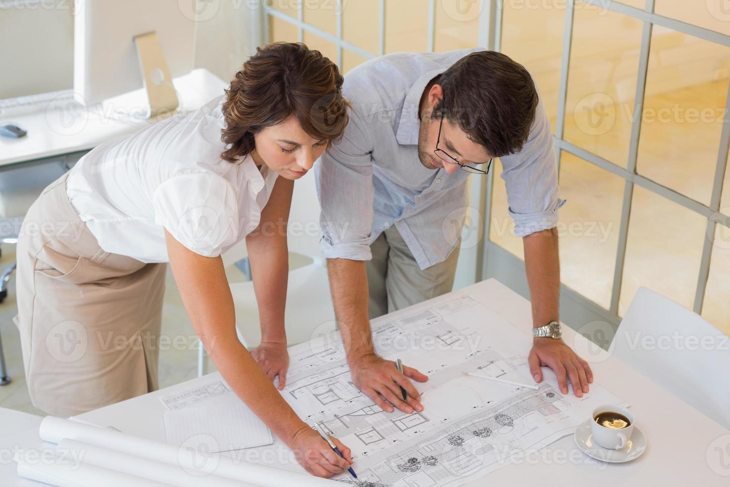 Geschäftsleute, die im Büro an Bauplänen arbeiten foto
