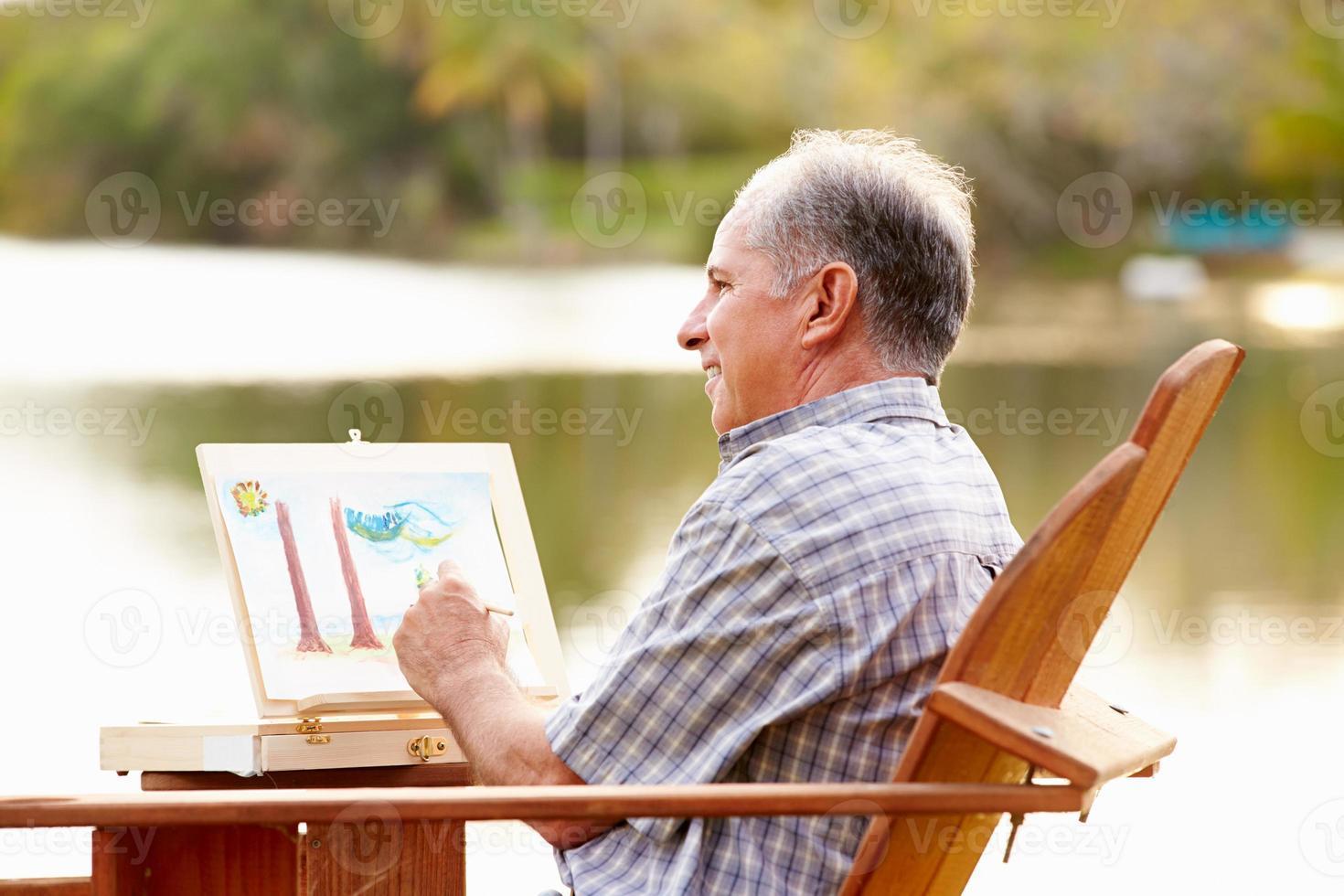 älterer Mann, der an der Tischmalereilandschaft im Freien sitzt foto