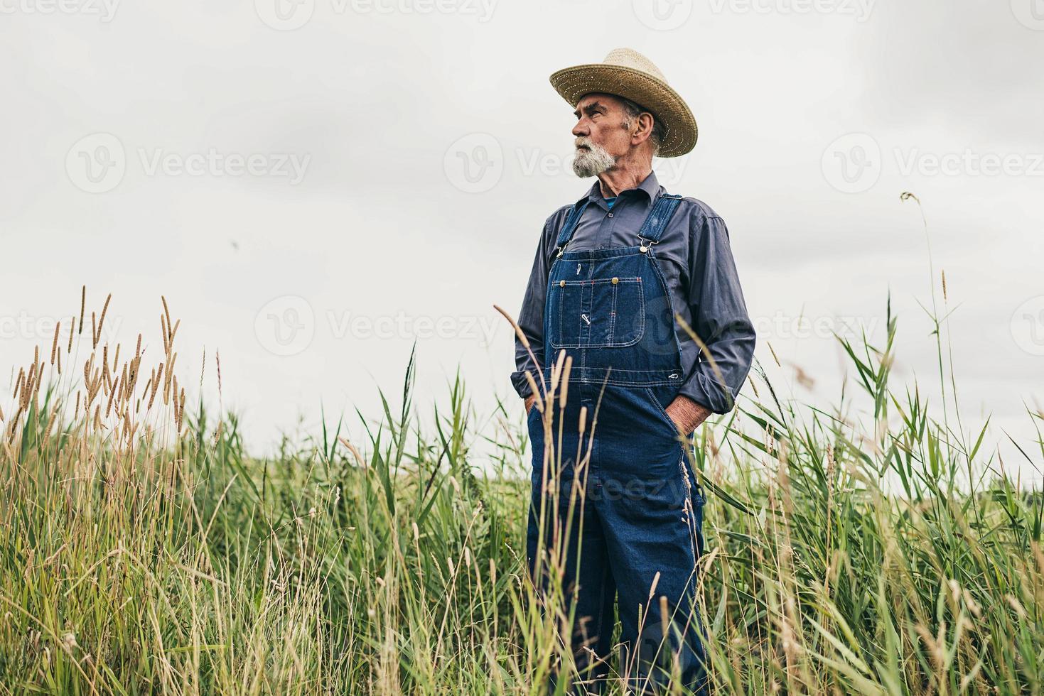 älterer männlicher Bauer mit Hut, der an der Farm steht foto