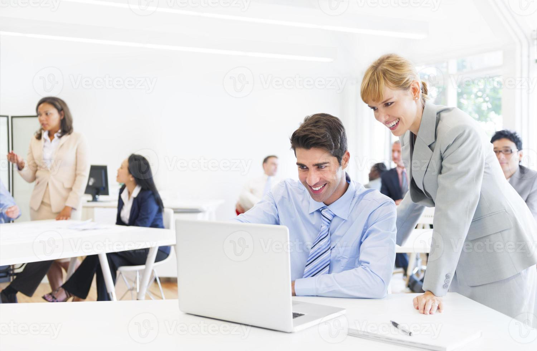 Chef führt ihren Angestellten vor den Laptop foto