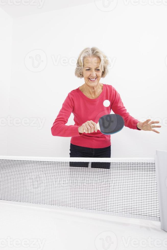 glückliche ältere Frau, die Tischtennis spielt foto