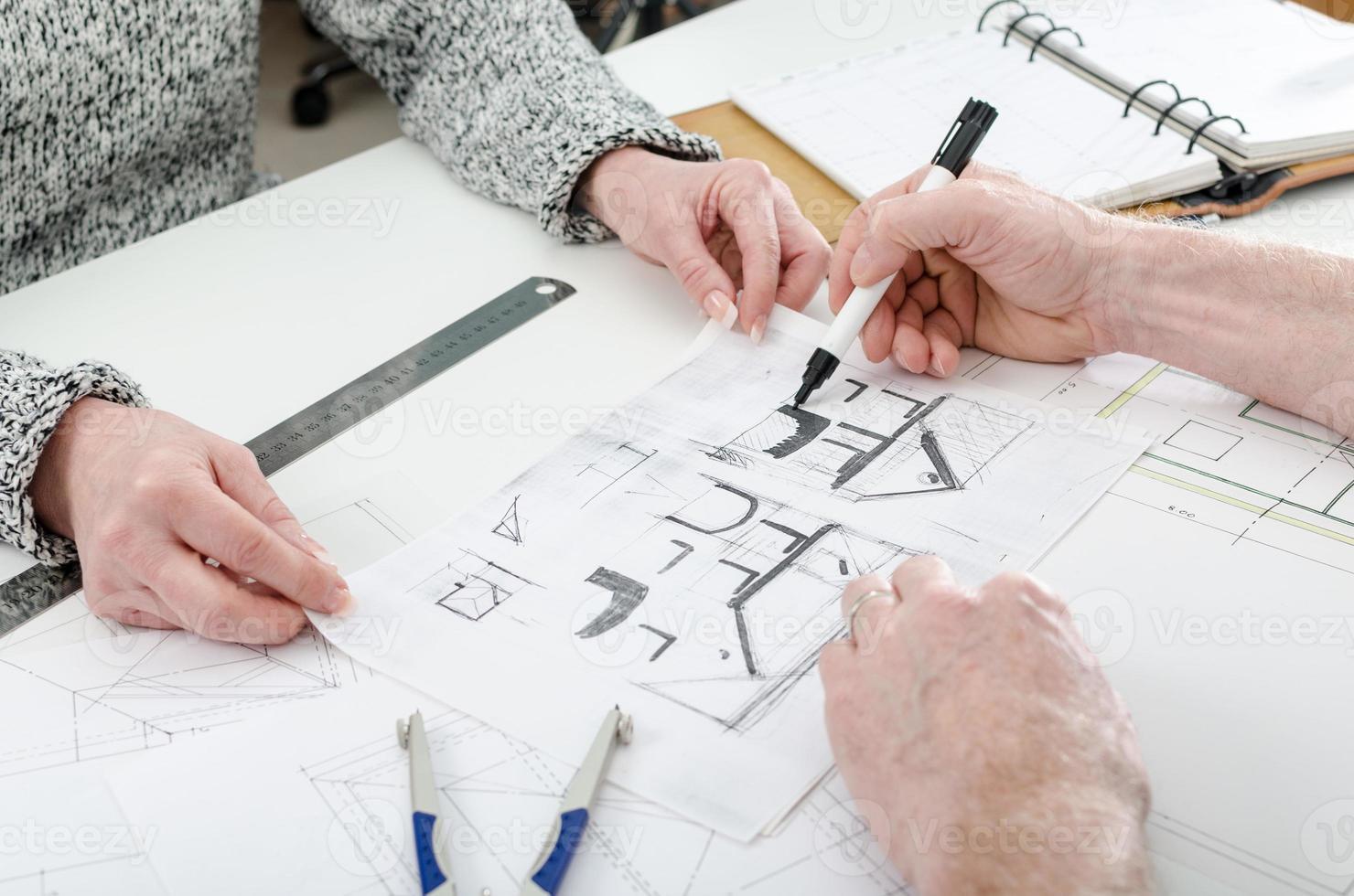 Architekt zeigt Hauspläne foto