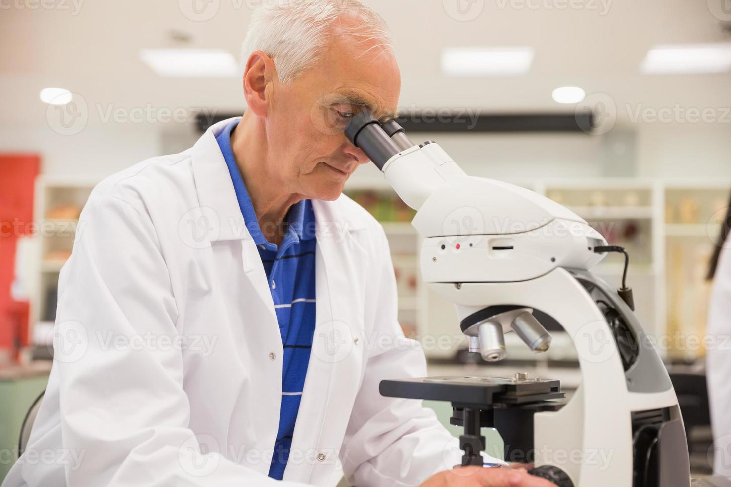 Medizinprofessor mit Mikroskop foto