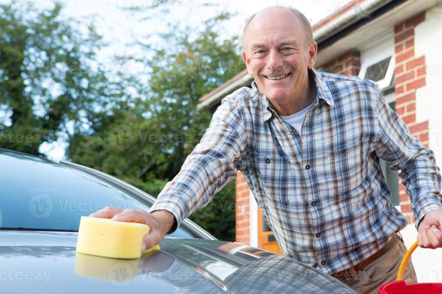 Porträt des älteren Mannes, der Auto wäscht foto