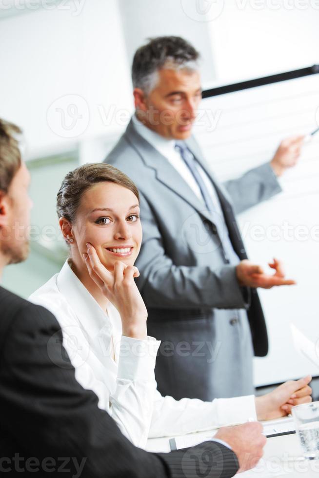 lächelnde Frau, die an einem Geschäftstreffen mit Kollegen sitzt foto